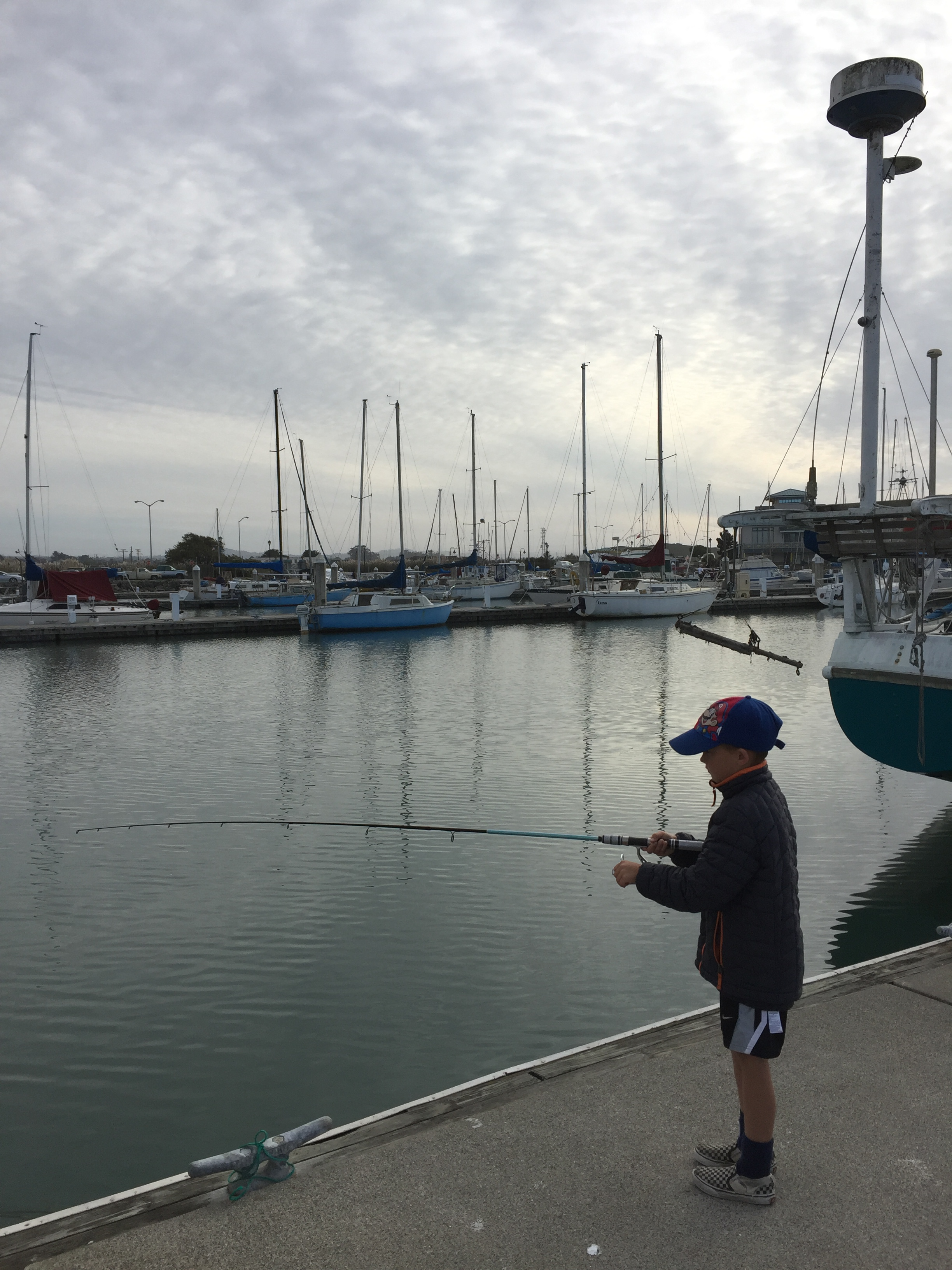 Image of boy fishing from pier